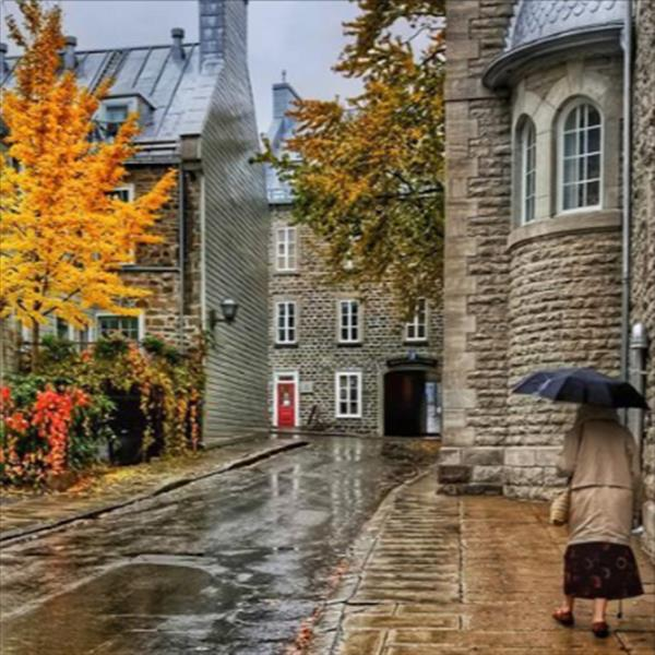 Touring Old Quebec City on a rainy day with vivid fall colors. The scene came alive as a woman hurried down the street with her umbrella.